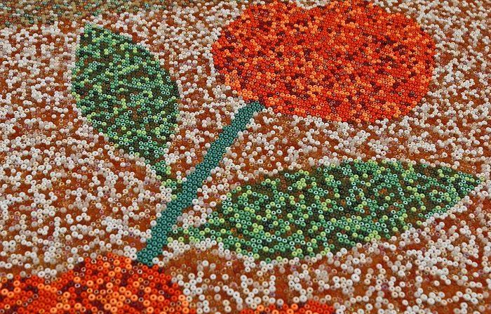 Un grupo de indígenas originarios del poblado de San Sebastián, en la sierra norte de Jalisco, trabaja durante 14 horas para dejar listas las 32 piezas que conforman el colorido mosaico hecho completamente a mano y con un peso aproximado de dos toneladas. EFE/Francisco Guasco