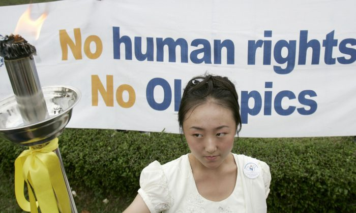 """Una activista sostiene una antorcha, su llama es símbolo de los DD.HH. universales, durante un relevo de antorcha """"alternativa"""" con motivo de destacar el historial de Derechos Humanos de China, en Kuala Lumpur el 25 de mayo de 2008. El relevo de la antorcha de DD.HH. fue en protesta por Los Juegos Olímpicos de 2008, debido al manejo por parte del gobierno chino de los disturbios en el Tíbet, la persecución a los practicantes de Falun Gong y sus vínculos con la junta militar de Myanmar, dijeron los organizadores. (TENGKU BAHAR / AFP / Getty Images)"""