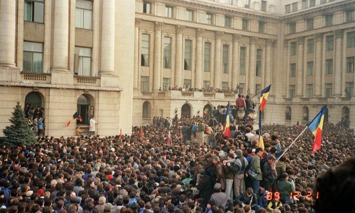 Ciudadanos de Bucarest agitan banderas rumanas en una manifestación anticomunista en la Plaza de la República, el 21 de diciembre de 1989, poco antes de la caída del régimen comunista. (AFP / Getty Images)