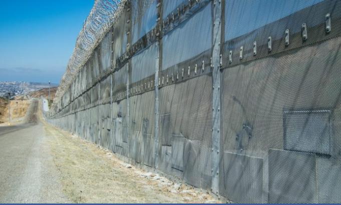 Los Muchos parches se alinean en la parte inferior de la barrera, donde los inmigrantes ilegales cortan la valla, a lo largo de la frontera de México con Estados Unidos en San Diego el 12 de julio de 2017. (Joshua Philipp / La Gran Época)