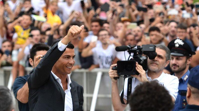 El futbolista portugués Cristiano Ronaldo saluda a sus seguidores cuando llega el 16 de julio de 2018 al centro médico Juventus en el estadio Alliance de Turín. (Miguel MEDINA / AFP/ Getty Images)