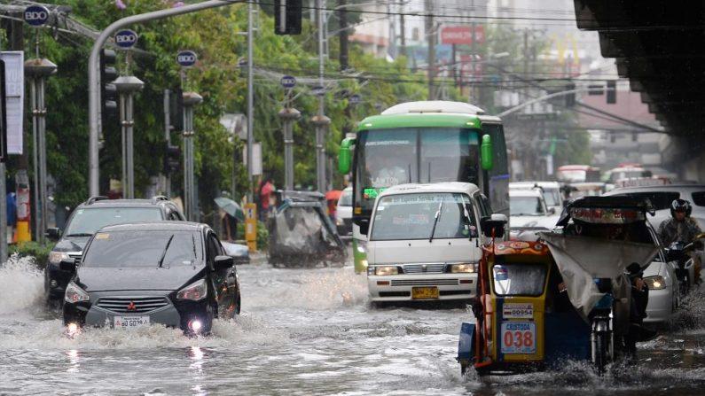 Los automovilistas conducen por una calle inundada en Manila el 17 de julio de 2018, cuando una depresión tropical, localmente llamada Henry, tocó tierra en el norte de la isla de Luzón y afectó las afueras de Manila y las provincias cercanas con lluvias monzónicas, según el informe de la oficina meteorológica. (TED ALJIBE / AFP / Getty Images)