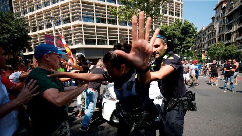 La policía municipal asegura la zona después que los taxistas que protestaban, intentaron impedir que un periodista se subiera a un vehículo de un servicio de transporte basado en aplicaciones, durante una huelga de taxistas en Barcelona el 25 de julio de 2018. (Foto de PAU BARRENA/AFP/Getty Images)