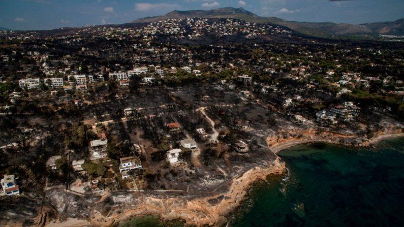 Una vista aérea muestra un área quemada después de un incendio forestal en la aldea de Mati, cerca de Atenas, el 26 de julio de 2018. Grecia contaba el costo del 26 de julio de sus incendios forestales más mortíferos en la memoria, mientras los equipos de emergencia buscaban desaparecidos en casas y vehículos incinerados, después de que se confirmó que al menos 81 personas murieron. ( SAVVAS KARMANIOLAS/AFP/Getty Images)