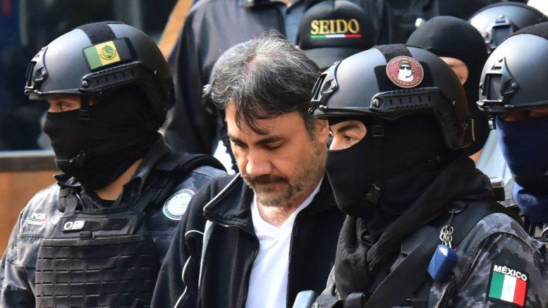 Agentes de la Agencia de Investigación Criminal y soldados del ejército mexicano escoltan al lugarteniente mayor del narcotraficante encarcelad, Joaquín Chapo Guzmán, Dámaso López (centro), después de ser arrestado en la Ciudad de México el 2 de mayo de 2017. (Crédito de STR/AFP/Getty Images)