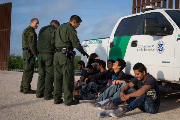 Agentes de la Patrulla Fronteriza atrapan a inmigrantes poco después de que estos cruzaran ilegalmente la frontera desde México, 26 de marzo de 2018. (LOREN ELLIOTT/AFP/Getty Images)