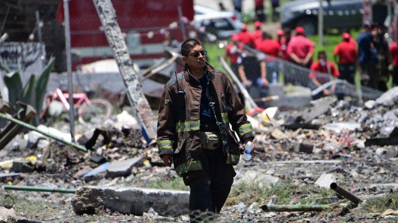 Un bombero camina en el sitio de la serie de explosiones en los almacenes de fuegos artificiales en Tultepec, México central, el 5 de julio de 2018.  (Foto de PEDRO PARDO/AFP/Getty Images)