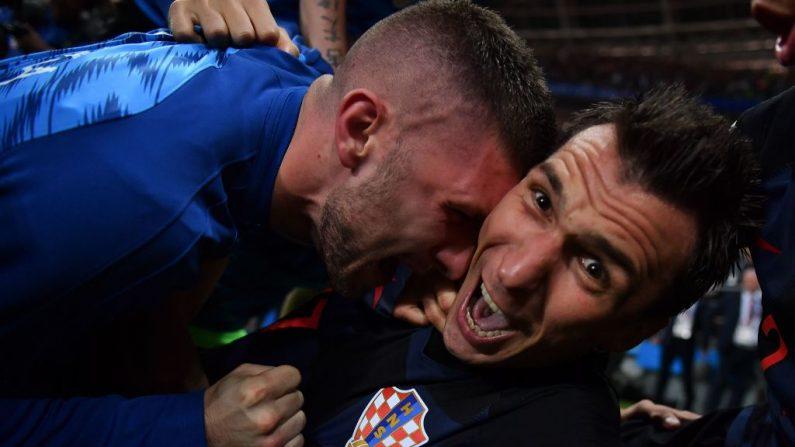 El delantero croata Mario Mandzukic (der) observa al fotógrafo Yuri Cortez en el suelo, mientras celebra con sus compañeros después de anotar el segundo gol de su equipo durante el partido de semifinales de la Copa Mundial Rusia 2018 entre Croacia e Inglaterra en el Estadio Luzhniki en Moscú el 11 de julio de 2018. (YURI CORTEZ / AFP / Getty Images)