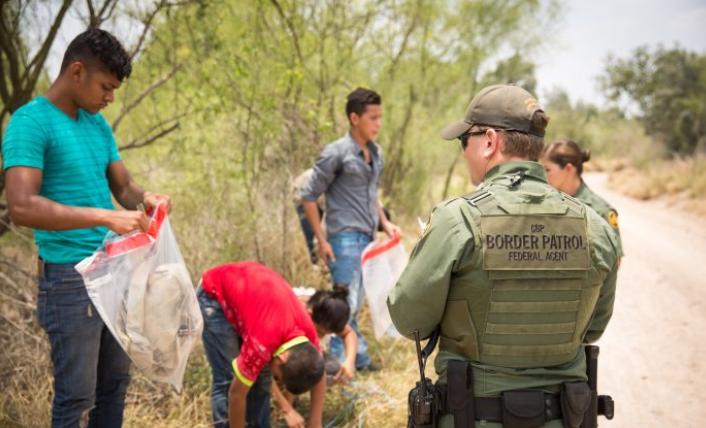 Agentes de la Patrulla Fronteriza hacen que los inmigrantes ilegales pongan sus pertenencias en bolsas de plástico para facilitar su proceso, antes de transportarlos al condado de Hidalgo, Texas, el 26 de mayo de 2017. (Benjamin Chasteen/The Epoch Times)