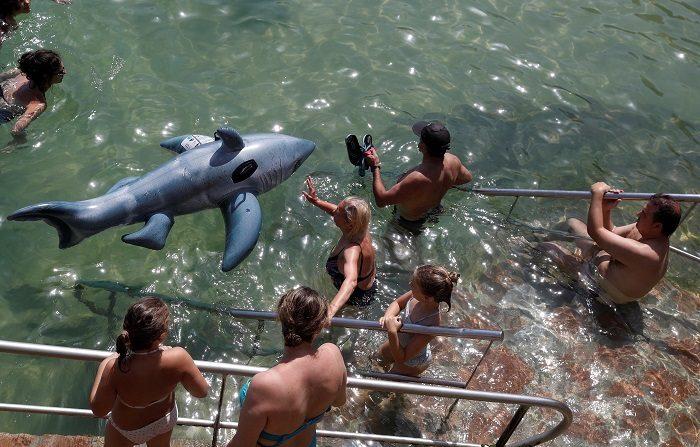 La OCU alerta del peligro de que los niños se bañen con figuras hinchables en el mar Donostiarras y visitantes disfrutan de la playa de La Concha de San Sebastián con una figura hinchable. EFE