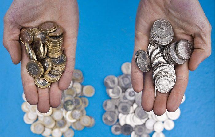 Los pensionaods destinan más del 70 % de sus ingresos a la vivienda. En la imagen, una persona sosteniendo en sus manos monedas de euro (izq) y monedas de franco suizo, en Zurich (Suiza). EFE/Archivo