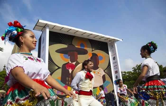 Mariachis y bailarinas se presentan hoy, lunes 20 de agosto de 2018, frente a un mosaico hecho con chaquiras, en la ciudad de Guadalajara Jalisco (México). Indígenas wixaritari del mexicano estado de Jalisco lograron hoy imponer un récord Guinness al mosaico de chaquiras (abalorios) más grande del mundo, con un mural de 81,55 metros cuadrados y dos toneladas de peso. EFE/Francisco Guasco