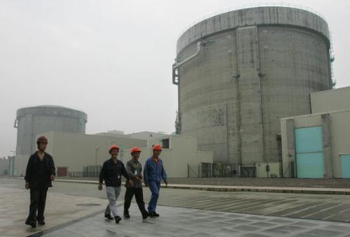 Trabajadores de la planta nuclear de Qinshan pasan frente a las estructuras de contención de reactores nucleares, en la ciudad de Jiaxing, provincia de Zhejiang, el 10 de junio de 2005. (Frederic J. Brown / AFP / Getty Images)