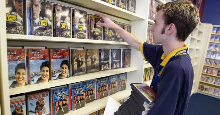 El empleado de Blockbuster, Mat Wangrow, arregla DVD en un estante dentro de una tienda de Blockbuster el 6 de enero de 2003 en Park Ridge, Illinois. (Foto de Tim Boyle/Getty Images)