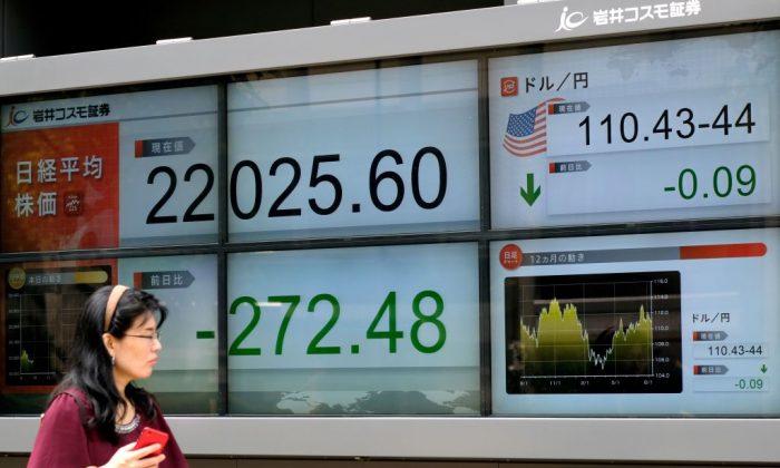 Un peatón pasa frente a una pantalla electrónica que muestra los precios de las acciones de la Bolsa de Valores de Tokio (izq.) y el tipo de cambio entre el yen y el dólar estadounidense (der.) en Tokio, el 13 de agosto de 2018. (Kazuhiro Nogi/AFP/Getty Images)