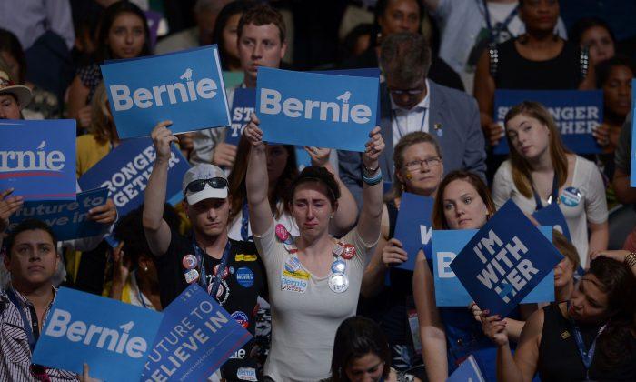 Simpatizantes del senador Bernie Sanders y Hillary Clinton con carteles en el día 1 de la Convención Nacional en el Centro Wells Fargo en Filadelfia el 25 de julio de 2016. (BRENDAN SMIALOWSKI/AFP/Getty Images)