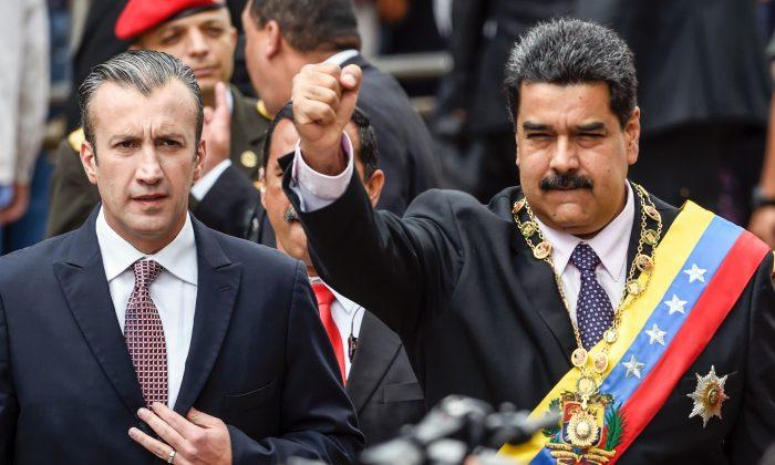 El presidente venezolano Nicolás Maduro (izq.) y el vicepresidente Tareck El Aissami saludan a los simpatizantes antes de la ceremonia en la que Maduro pronunció un discurso en el que repasó su año en el cargo ante el Tribunal Supremo de Justicia en Caracas el 15 de enero de 2017. (JUAN BARRETO/AFP/Getty Images)