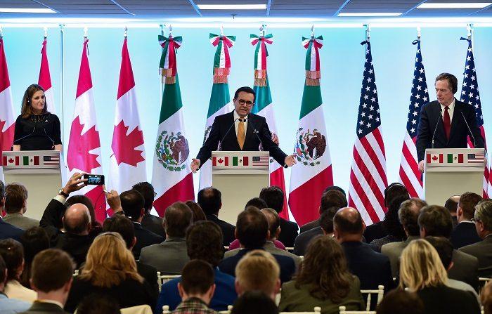 """Los representantes están enfrente la bandera de Canadá, México y Estados Unidos sobre el Tratado de Libre Comercio de América del Norte (TLCAN). """"(Las negociaciones con México) no han acabado todavía pero soy optimista de que podemos llegar"""" a un acuerdo esta semana, dijo hoy un alto funcionario de la Casa Blanca que pidió el anonimato a un reducido grupo de medios. (Photo credit should read RONALDO SCHEMIDT/AFP/Getty Images)"""