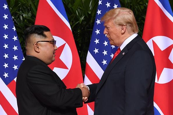 El líder de Corea del Norte, Kim Jong Un (izq.), da la mano al presidente de Estados Unidos, Donald Trump (der.), al comienzo de su histórica cumbre EE.UU.-Corea del Norte, en el Hotel Capella de la isla de Sentosa, en Singapur, el 12 de junio de 2018. (SAUL LOEB/AFP/Getty Images)