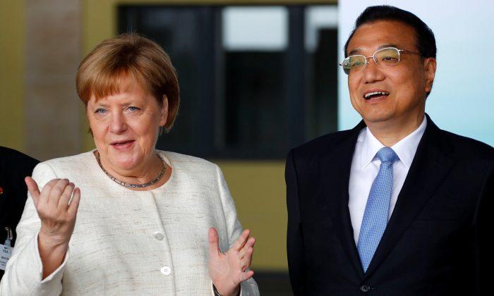 La canciller alemana Angela Merkel (izq) y el premier chino Li Keqiang en una presentación de autos autónomos en el ahora en desuso histórico aeropuerto Tempelhof en Berlin, el 10 de julio de2018. (FABRIZIO BENSCH/AFP/Getty Images)