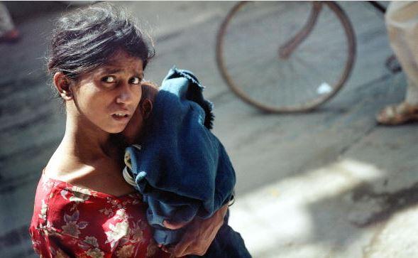 Una mujer india lleva a su niño a lo largo de una calle concurrida el 26 de septiembre de 2005 en Nueva Delhi, India. Aunque India ocupa solo el 2.4% de la superficie terrestre del mundo, es compatible con más del 15% de la población mundial. Según estudios de población global, el subcontinente superará a China para ser el país más poblado del mundo en 20 años. (Foto por Uriel Sinai / Getty Images)