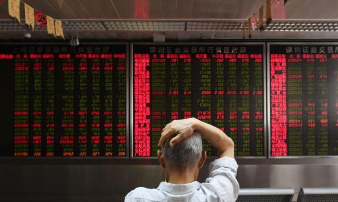 Un hombre verifica los movimientos de precios de acciones en una compañía de valores en Beijing, el 4 de julio de 2018. (Greg Baker / AFP / Getty Images)
