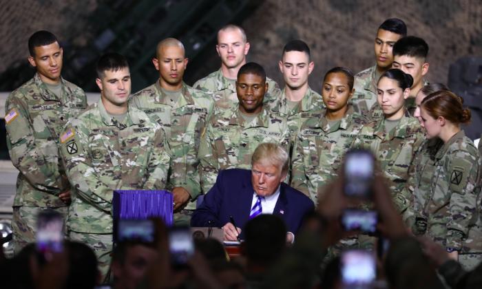 Donald Trump firma el Acta de Autorización de Defensa Nacional en Fort Drum, NY, el 13 de agosto de 2018. (Charlotte Cuthbertson/La Gran Época)