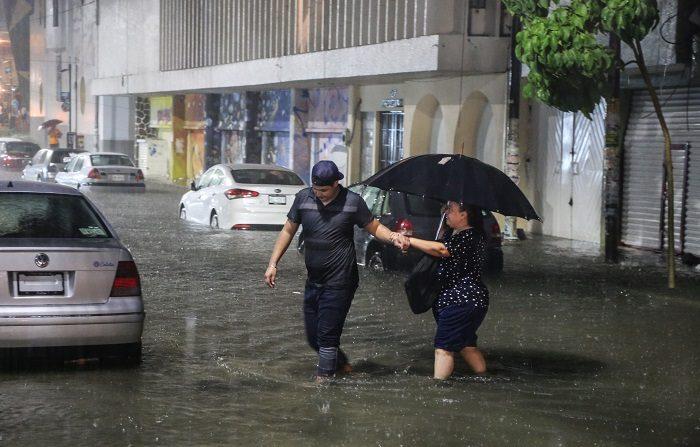 Dos personas cruzan una calle inundada, en el puerto de Acapulco, en el estado de Guerrero (México). EFE/David Guzmán.
