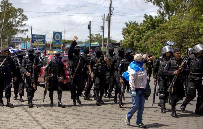 Fotografía registró a escuadrón de la policía nacional nicaragüense al bloquear una marcha opositora, en Managua (Nicaragua). EFE