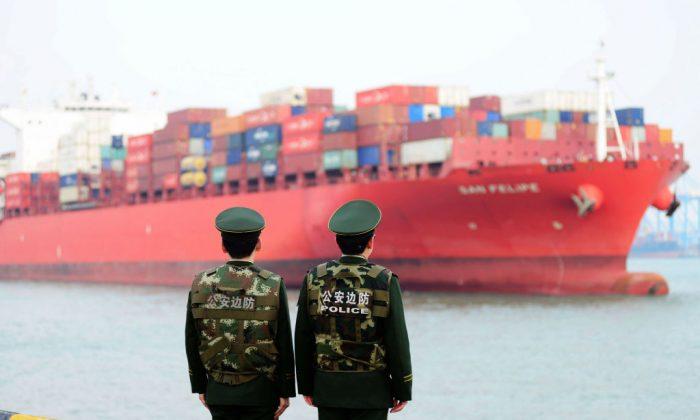 Oficiales de policía chinos observan un barco de carga en el Puerto Qingdao en la provincia china de Shandong, el 8 de marzo de 2018. (AFP/Getty Images)