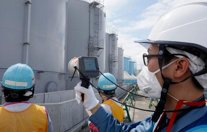 Un miembro del personal de la Compañía de Energía Eléctrica de Tokio mide los niveles de radiación alrededor de los tanques de almacenamiento de agua contaminada por la radiación en la planta de energía nuclear Fukushima Dai-ichi de la Compañía de Energía Eléctrica de Tokio (TEPCO) el 27 de julio de 2018, que quedó invalidada por el tsunami, en Okuma, prefectura de Fukushima. (KIMIMASA MAYAMA/AFP/Getty Images)