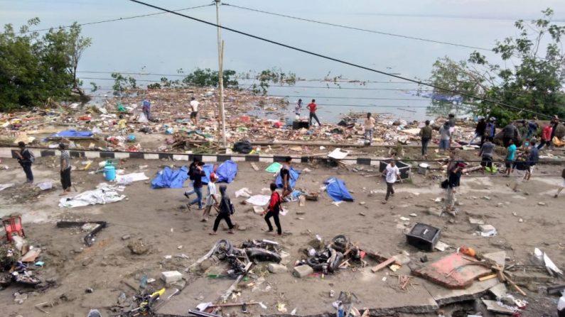 La gente camina junto a cadáveres (cobertura azul) un día después de que un terremoto y un tsunami golpearan a Palu, en la isla de Sulawesi el 29 de septiembre de 2018. Los rescatistas se apresuraron a llegar al centro de Indonesia y evaluar el daño después de que un fuerte terremoto derribó varios Edificios. Los lugareños que pudieron huir de los hogares desaparecidos se fueron a terrenos más altos. (OLA GONDRONK AFP/Getty Images)