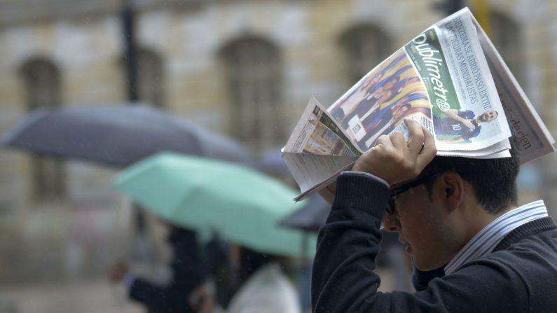 Un hombre se cubre de la lluvia con un periódico en Bogotá, Colombia, junio de 2014. (RAUL ARBOLEDA/AFP/Getty Images)