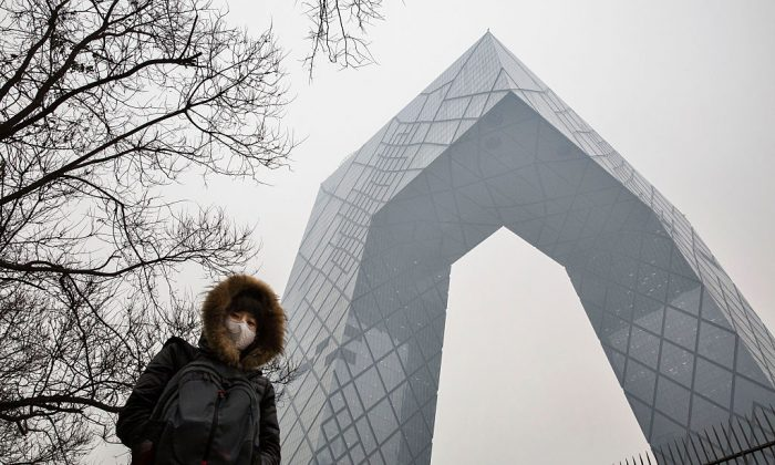 Una mujer china con un barbijo para protegerse de la contaminación frente al edificio de la CCTV en Beijing el 8 de diciembre de 2015. (Kevin Frayer/Getty Images)