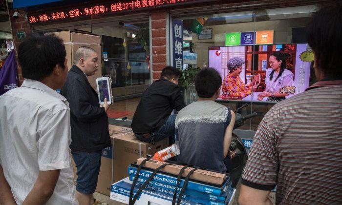Hombres chinos viendo un programa de televisión a través de la vidriera de una tienda de electrodomésticos en Wuhan, provincia de Hubei, China, el 15 de mayo de 2017. (Kevin Frayer/Getty Images)
