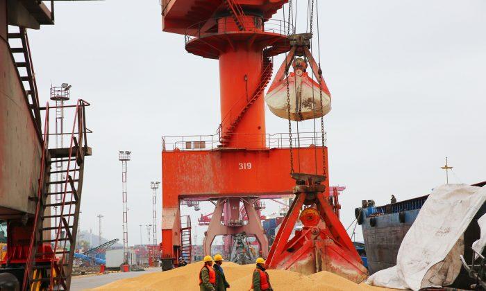 Trabajadores caminando frente a la soja importada en el puerto de la ciudad de Nantong, provincia de Jiangsu, el 4 de abril de 2018. (AFP/Getty Images)