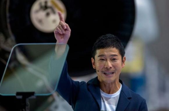El multimillonario japonés Yusaku Maezawa señala hacia el espacio cerca de un cohete Falcon 9 durante el anuncio de Elon Musk de ser el primer pasajero privado que volará alrededor de la Luna a bordo del vehículo de lanzamiento SpaceX BFR, en la sede central y fábrica de cohetes SpaceX el 17 de septiembre de 2018 en Hawthorne, California. (DAVID MCNEW/AFP/Getty Images)