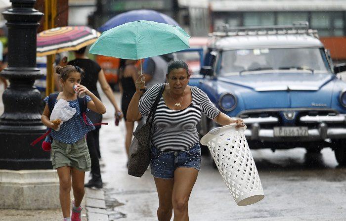 Personas se cubren de la lluvia hoy, lunes 8 de octubre del 2018, antes de la llegada de la tormenta tropical Michael, en La Habana (Cuba). Las autoridades cubanas decretaron la primera fase del protocolo ante huracanes en cinco provincias del oeste de la isla, incluida La Habana, ante la cercanía de la tormenta tropical Michael, que previsiblemente se convertirá hoy en huracán y dejará fuertes lluvias, viento e inundaciones costeras. EFE/Yander Zamora