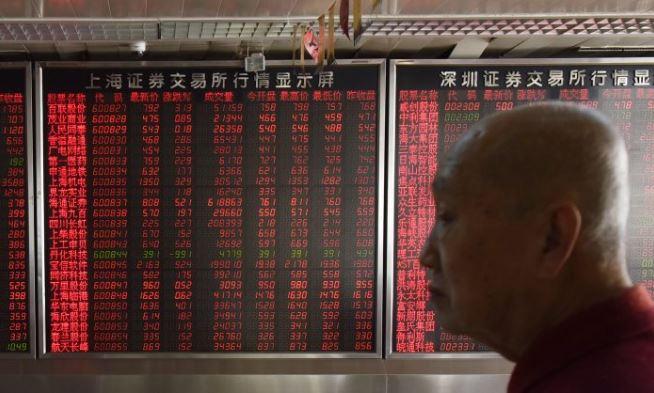 Un inversionista frente a una pantalla que muestra los precios de las acciones en una compañía de valores en Beijing el 19 de octubre. (Greg Baker / AFP / Getty Images)