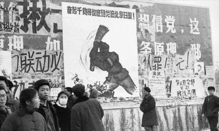 """Un pequeño grupo de jóvenes chinos pasa junto a varios dazibao, pancartas revolucionarias, durante la """"Gran Revolución Cultural Proletaria"""" en el centro de Beijing,  en febrero de 1967. (JEAN VINCENT/AFP/Getty Images)"""