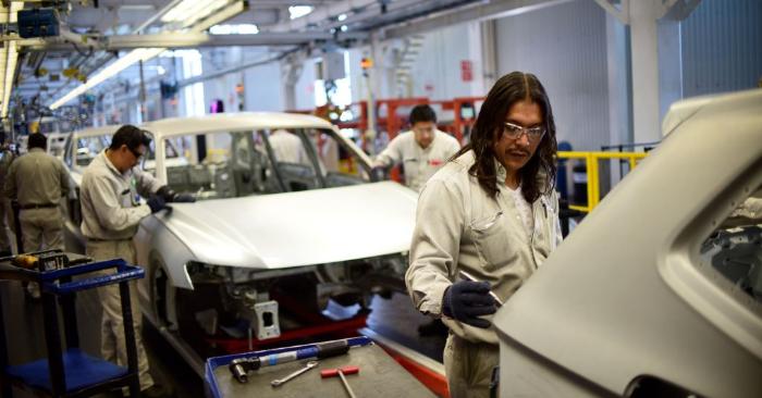 Trabajadores en la línea de montaje del modelo Tiguan, en la planta automotriz de Volkswagen en Puebla, México central, el 16 de marzo de 2018. (Foto de PEDRO PARDO/AFP/Getty Images)
