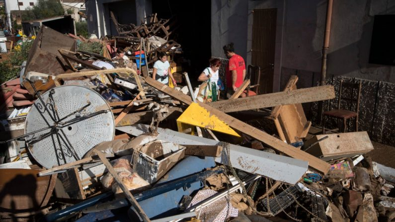 """Locals walk on a street full of debris in Sant Llorenc des Cardassar on the Spanish Balearic island of Majorca on October 11, 2018. - The death toll in flash floods that hit Spain's holiday island of Majorca rose to 12 today after the bodies of a man and a woman were discovered, """"possibly"""" those of two missing Germans, police said. (Photo by JAIME REINA / AFP)        (Photo credit should read JAIME REINA/AFP/Getty Images)"""