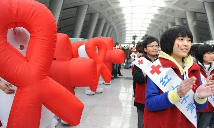 Voluntarios de la Cruz Roja China participan en un evento de sensibilización sobre el SIDA en el Día Mundial del SIDA en la estación de trenes de Beijing, para pedir un mejor apoyo gubernamental a las víctimas del VIH/SIDA en China, el 1 de diciembre de 2009. (AFP/AFP/Getty Images)
