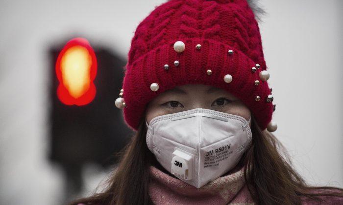 Una mujer usa una máscara para protegerse de la contaminación mientras espera para cruzar la calle en medio de una gran cantidad de smog en Beijing, China, el 8 de diciembre de 2015.  (Kevin Frayer/Getty Images)