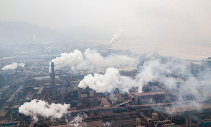 Esta vista aérea tomada desde un drone muestra la contaminación emitida por las fábricas de acero en Hancheng, provincia de Shaanxi, China, el 17 de febrero de 2018. (Fred Dufour/AFP/Getty Images)