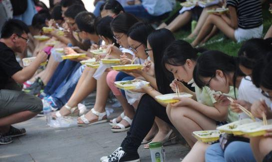 El 29 de julio de 2015, postulantes de posgrado se sientan en el suelo y comen fuera de un salón de actos en Jinan, provincia de Shandong, China. (VCG / VCG a través de Getty Images)