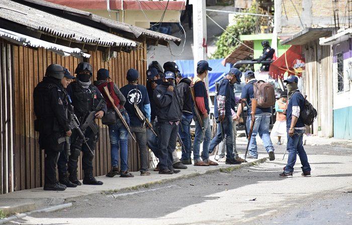 Autodefensas se observan en la población de Filo de Caballos, en el estado de Guerrero (México) hoy, tras tomar el control luego de que grupos armados asolaran a los habitantes. Al menos siete personas murieron y otras cinco resultaron heridas en el municipio mexicano Eduardo Neri, en un enfrentamiento entre policías comunitarios y presuntos delincuentes, informó hoy el coordinador del Frente de Policías Comunitarias del Estado de Guerrero (FPCEG). El conflicto se produjo cuando al menos 3.000 integrantes del FPCEG entraron en la comunidad de Filo de Caballos, sureño estado de Guerrero, la tarde del domingo y tomaron el control de la seguridad en la zona, que había sido asolada por grupos delincuenciales. EFE/STR