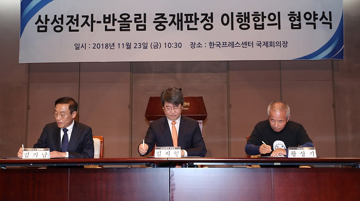 Kim Ki-nam (i), presidente y CEO de Samsung Electronics, se reúne con representantes las víctimas que se enfermaron mientras trabajaban en las plantas de la compañía, tras firmar un acuerdo de resolución hoy en Seúl (Corea del Sur). EFE