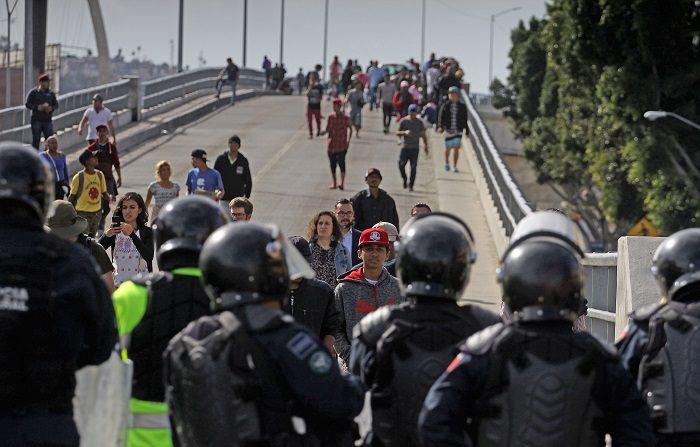 Centenares de migrantes de la caravana de centroamericanos rompió un cerco policial con el afán de llegar a la garita de El Chaparral, en la frontera de la mexicana Tijuana con San Ysidro (Estados Unidos). EFE/Joebeth Terriquez