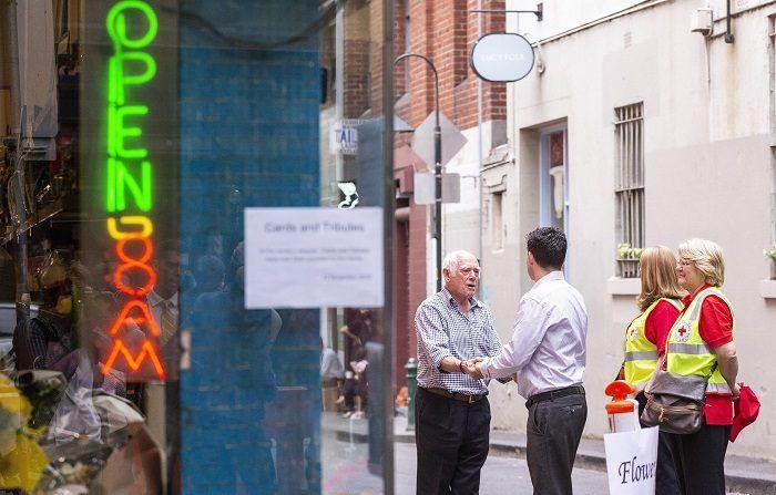 Nino Pangrazio (i), dueño de Pellegrini's Espresso Bar, saluda a clientes durante la reapertura del local al público hoy, en Melbourne (Australia). La cafetería era copropiedad de Sisto Malaspina, quien fue apuñalado a muerte por Hassan Khalif Shire Ali en un ataque terrorista el pasado 9 de noviembre. EFE/ Daniel Pockett PROHIBIDO SU USO EN AUSTRALIA Y NUEVA ZELANDA